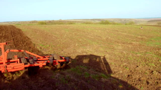 Farmer in tractor plows Russia steadicam motion agriculture soil the ground preparing land with seedbed cultivator as part of pre seeding activities in early spring season of lifestyle agricultural works at farmlands. agriculture concept - vídeo