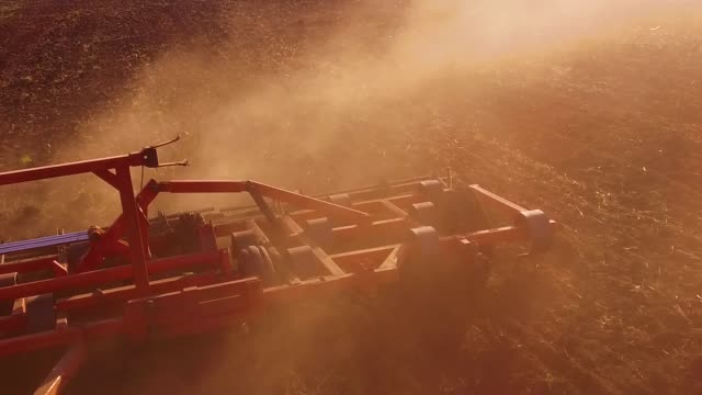 Farmer in tractor plows steadicam slow motion Russia agriculture soil the ground preparing land with seedbed cultivator as part of pre seeding activities in early spring lifestyle season of agricultural works at farmlands. agriculture concept - vídeo