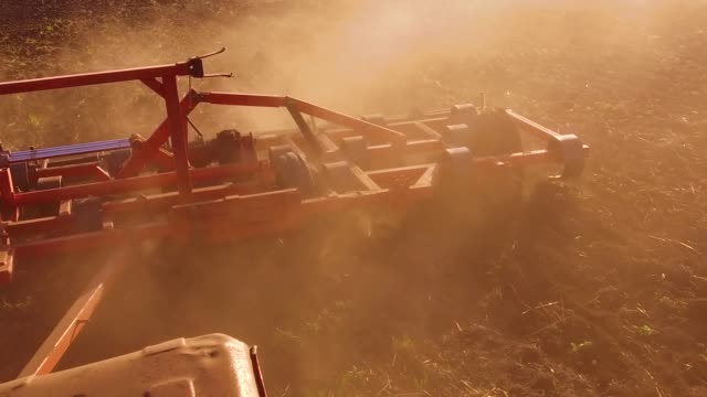 Farmer in tractor plows steadicam slow motion Russia agriculture soil the ground preparing land with seedbed cultivator as part of pre seeding activities in early spring season of lifestyle lifestyle agricultural works at farmlands. agriculture concept - vídeo