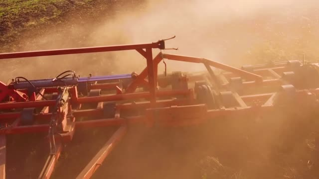 Farmer in tractor plows steadicam slow motion Russia agriculture soil the ground preparing land with seedbed cultivator as part of pre seeding activities in early spring season of lifestyle agricultural works at lifestyle farmlands. agriculture concept - vídeo