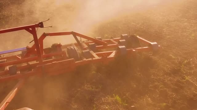 Farmer in tractor plows steadicam slow motion Russia agriculture soil the ground preparing land with seedbed cultivator as part of pre seeding activities in early spring season of lifestyle agricultural works lifestyle at farmlands. agriculture concept - vídeo
