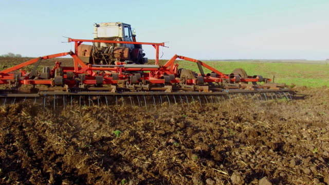 Farmer in tractor soil plows Russia steadicam motion agriculture the ground preparing land with seedbed cultivator as part of pre seeding activities in early spring season of agricultural works at farmlands. agriculture concept lifestyle - vídeo