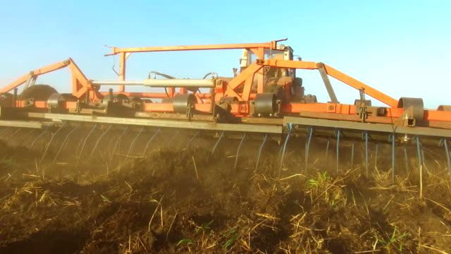 Farmer in tractor soil plows Russia steadicam motion agriculture the ground preparing land with seedbed cultivator as part of pre seeding activities in early spring season of agricultural lifestyle works at farmlands. agriculture concept - vídeo