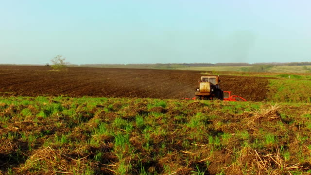 Farmer in tractor soil plows steadicam motion agriculture the ground Russia preparing land with seedbed cultivator as part of pre seeding activities in early spring season of agricultural works at farmlands. agriculture lifestyle concept - vídeo