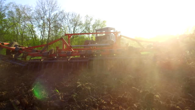 Farmer in tractor soil plows steadicam motion agriculture the ground Russia preparing land with seedbed cultivator as part of pre seeding activities lifestyle in early spring season of agricultural works at farmlands. agriculture concept - vídeo