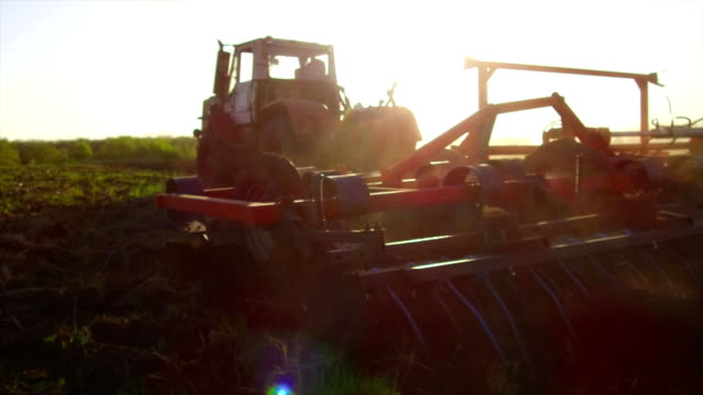 Farmer in tractor soil plows steadicam motion agriculture the ground Russia preparing land with seedbed cultivator as part of pre seeding activities in early spring season of agricultural works at lifestyle farmlands. agriculture concept - vídeo