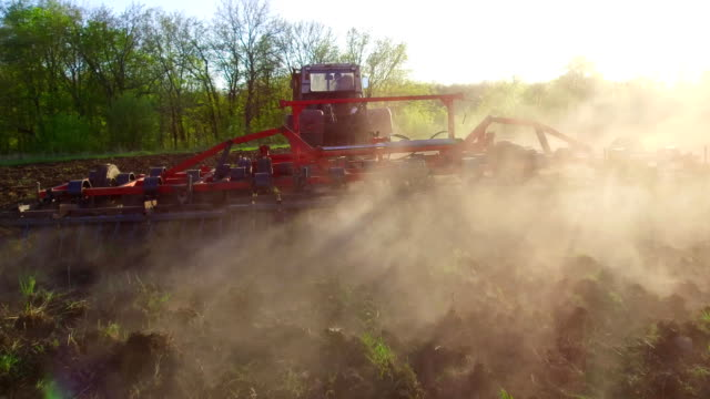 Farmer in tractor soil plows steadicam motion agriculture the ground Russia preparing land with seedbed cultivator as part of pre seeding activities in lifestyle early spring season of agricultural works at farmlands. agriculture concept - vídeo