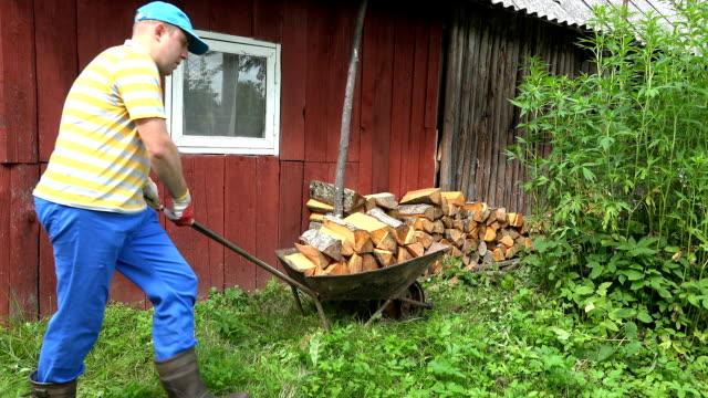 çiftçi adam el arabası taşımak ve ahşap evin yakınında yakacak odun boşaltın. 4k - şömine odunu stok videoları ve detay görüntü çekimi