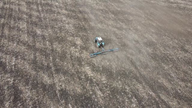 Farmer on a tractor plows the field. Top view from drone Farmer on a tractor plows the field. Top view from drone harrow agricultural equipment stock videos & royalty-free footage