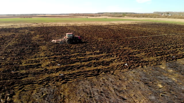 Farmer on a tractor prepares the land using a seeder-cultivator, agribusiness A distant tractor cultivates the soil for planting in early spring, leaving a fresh track on a wet plowed field. The concept of agribusiness agricultural occupation stock videos & royalty-free footage