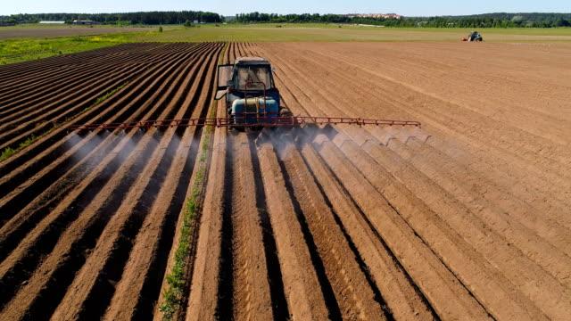 vidéos et rushes de agriculteur sur un tracteur vaporise labours d'engrais et produits chimiques - herbicide