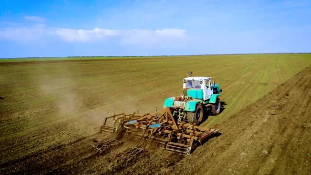 Jordbrukaren på stora traktor odlar fält och förbereder jord för sådd grödor video