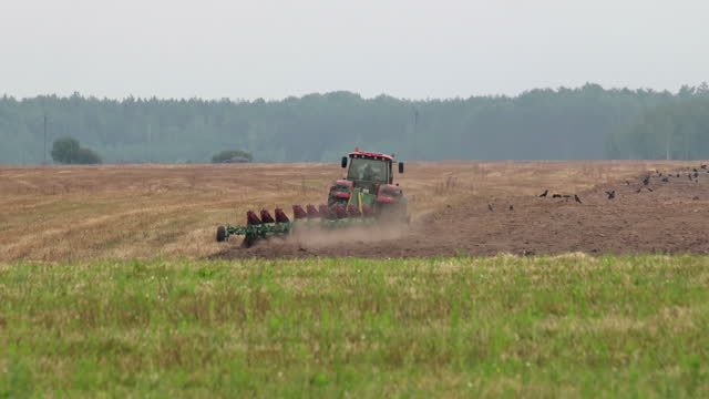 Farmer plows the fertile soil with a revolving multi-plow in a spring field in cloudy weather