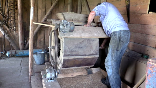 farmer processed grain with old hand cleansing harp in barn video