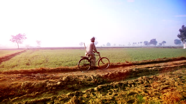 Farmer riding cycle to the filed video