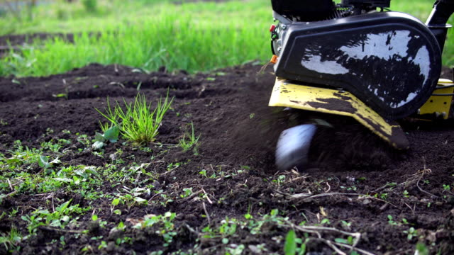 Farmer rips the ground with a cultivator Side view of tines motorized cultivator rips ground.Farmer's legs in black boots are buried in loose soil, preparation for landing. plow stock videos & royalty-free footage