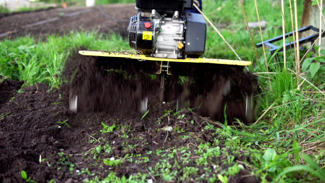 Farmer rips the ground with a cultivator Close up of tines motorized cultivator rips ground.Farmer's legs in black boots are buried in loose soil, preparation for landing. plow stock videos & royalty-free footage