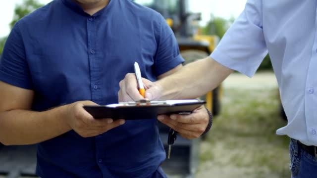 stockvideo's en b-roll-footage met boer ondertekening van de overeenkomst over het kopen van de trekker - shovel