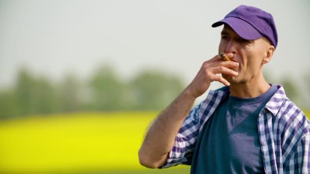 farmer smoking cigar while removing cap at farm - кепка стоковые видео и кадры b-roll