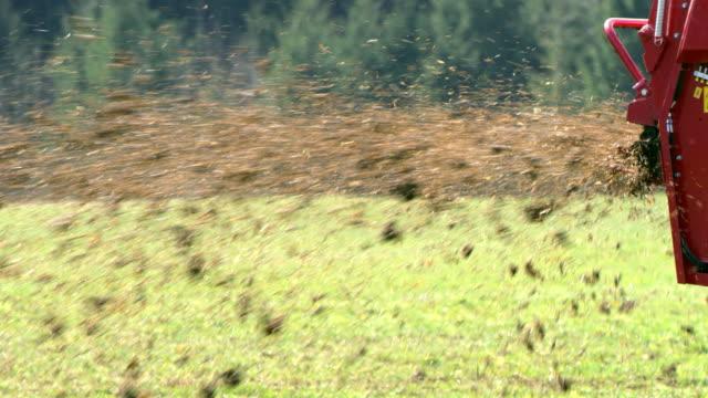 slo mo farmer spreading manure over the grass - rozkładać filmów i materiałów b-roll
