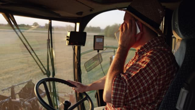 farmer talking on smart phone and driving combine harvester,slow motion - trattore video stock e b–roll