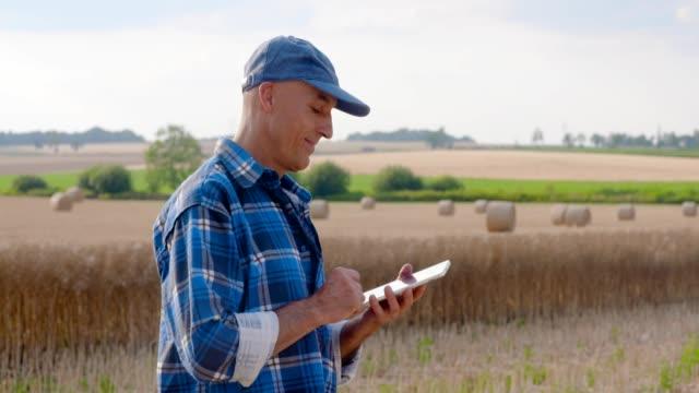 vídeos de stock e filmes b-roll de farmer uses a tablet computer at farm. farmer uses tablet while looking at crops. - colher atividade agrícola