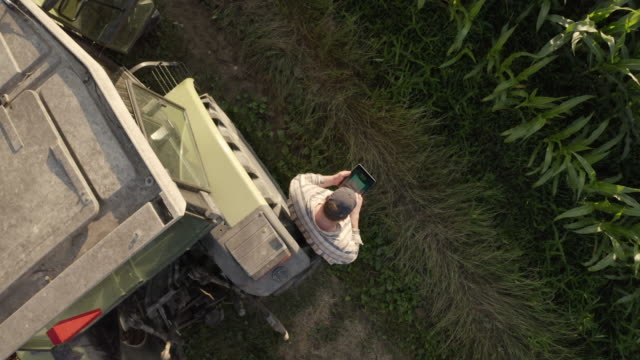AERIAL Farmer using a tablet beside a tractor parked on the edge of a field.