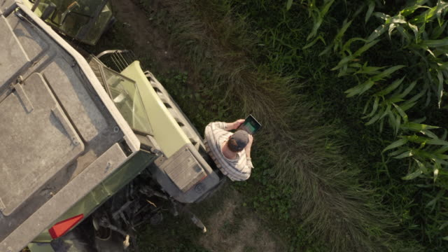 AERIAL Farmer using a tablet beside a tractor parked on the edge of a field. video