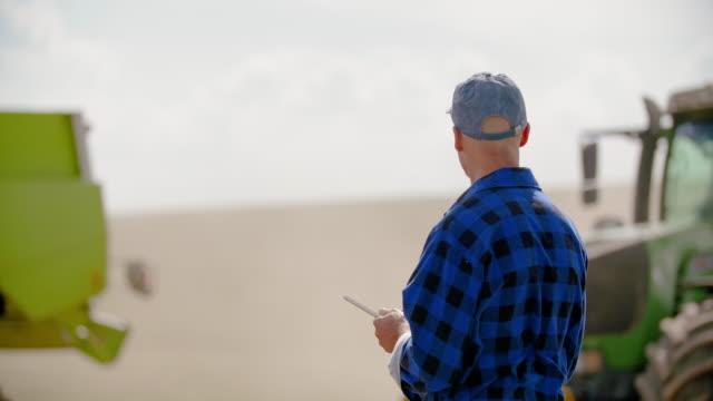 vidéos et rushes de agriculteur à l'aide de tablette numérique tout en examinant le champ - équipement agricole