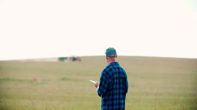 Farmer using digital tablet while examining field