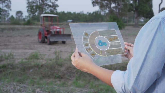 farmer using portable tablet computer to inspect the agricultural engine - голографический стоковые видео и кадры b-roll