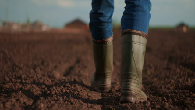 A farmer walks across a field in rubber boots on a blurred background of the tractor in motion. Concept of: Rubber boots, Lifestyle, Farmer, Slow Motion, Fields