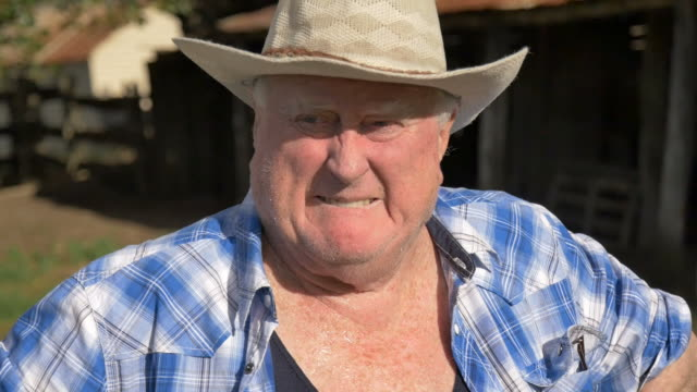 Farmer with hat looking at his farm on hot day video