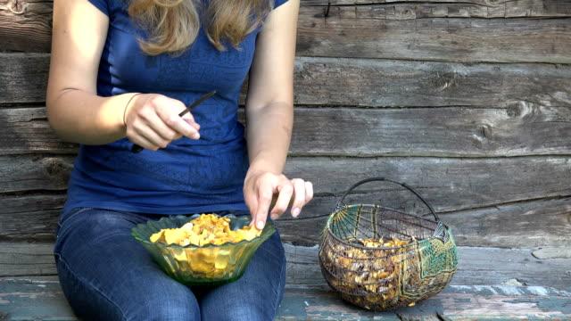bonde kvinnan händer ta gul kantareller svamp från korg och ren med kniv nära landsbygden rostiga hus väggen. statisk närbild skott. 4k - höst plocka svamp bildbanksvideor och videomaterial från bakom kulisserna