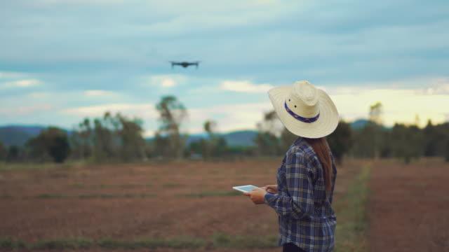 水田テラス上のドローン農業技術を制御するデジタルタブレットを持つ農家の女性 - モノのインターネット点の映像素材/bロール