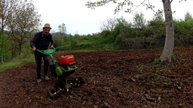 Farmer working with roto tiller & cultivator Farmer working with roto tiller & cultivator harrow agricultural equipment stock videos & royalty-free footage
