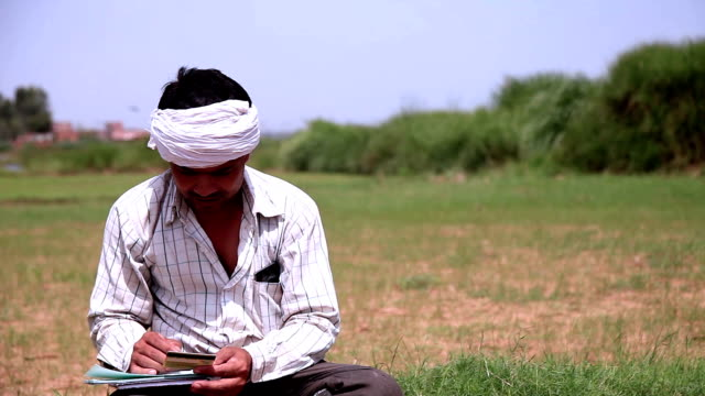 Farmer writing on paper Young farmer Sitting in nature & writing on the paper. He is holding his debit card on his hand while writing on the paper. haryana stock videos & royalty-free footage