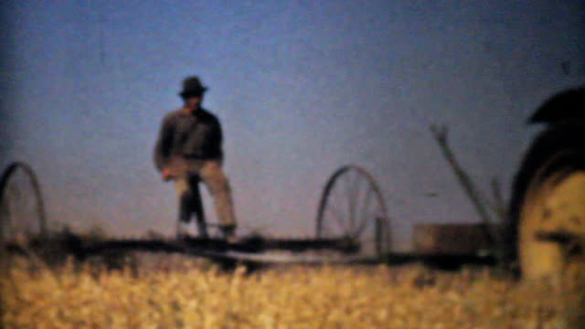 farmers harvesting fields with tractors-1940 vintage 8mm film - 移動圖像 個影片檔及 b 捲影像