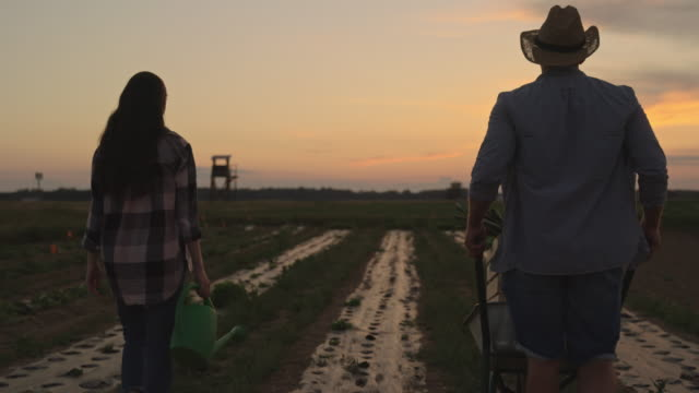 SLO MO Farmers walking away after all the work is done on the field at dusk