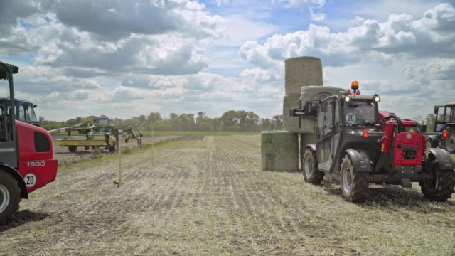 Farming tractor loading haystacks on agricultural field video
