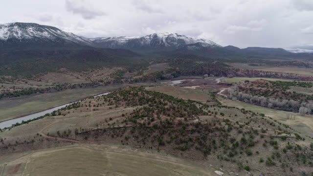 farmlands in colorado mountains, nearby mccoy, and colorado river, in the early spring. aerial drone video with the panoramic and descending camera motion. - ranczo filmów i materiałów b-roll