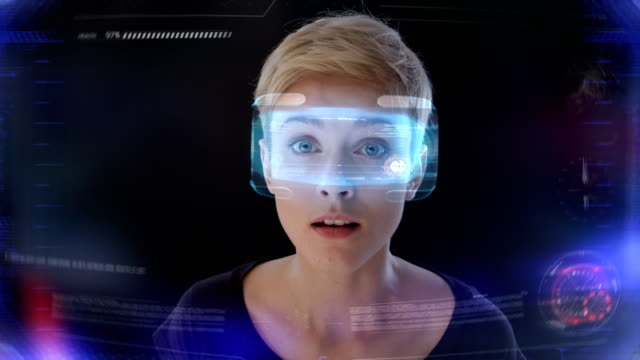 Fascinating virtual reality Woman isolated on black looking around in virtual, imaginary world. Wearing holographic virtual reality glasses. Frowning arts culture and entertainment stock videos & royalty-free footage
