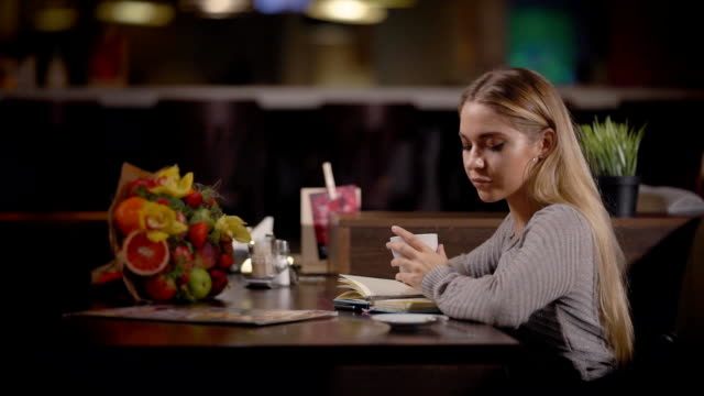Fascinating woman sits in a cafe all alone Amazing woman sits in a cafe with open diary on a table and fruit bouquet. She takes a menu on table and goes through it to order something. menu stock videos & royalty-free footage
