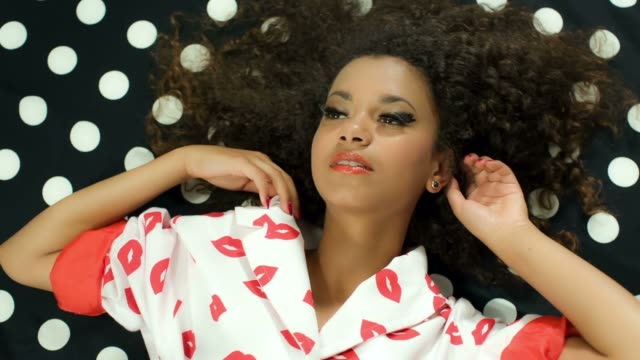 Fashion beauty portrait of young black beautiful model lying on dots pattern. Portrait of young black beautiful woman posing on black and white polka dots pattern. Fashion shot. Pin up style. Colors and black and white polka dots pattern. Pin up hairstyle. View from the top. eyelash stock videos & royalty-free footage