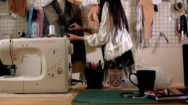 vídeos y material grabado en eventos de stock de diseñador de moda en el trabajo en estudio, fijando a la tela sobre maniquí - bocetos de diseños de moda