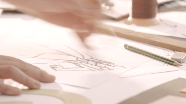 Fashion designer drawing in a studio. Woman's hand draws on paper. Close-up video