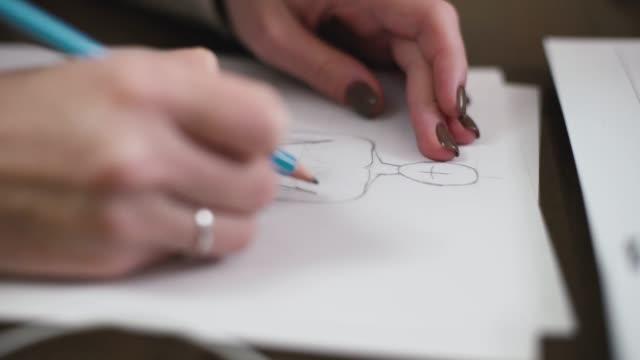modedesigner ritning modell för kläder skiss. hand av kvinnliga skräddare ritning mönster på papper i sin studio - blyertspenna bildbanksvideor och videomaterial från bakom kulisserna
