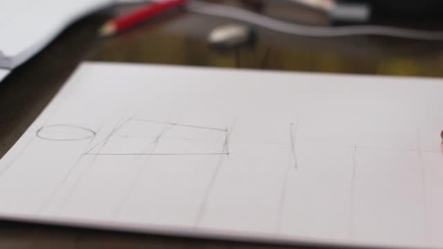 vídeos y material grabado en eventos de stock de modelo de dibujo de diseñador de moda para boceto de ropa. mano de patrón de dibujo a medida femenina en papel en su estudio - bocetos de diseños de moda