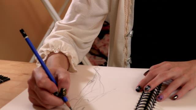 vídeos y material grabado en eventos de stock de empresario de diseñador de moda dibujo de estudio, de cerca en las manos - bocetos de diseños de moda