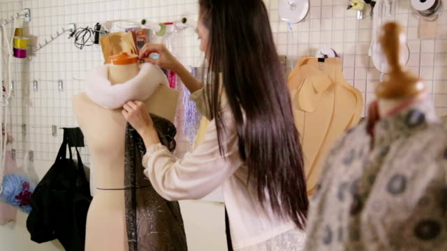 Fashion designer in studio pinning clothes on mannequin side view showing to offcamera client Fashion designer in studio pinning clothes on mannequin side view showing to offcamera client fabric swatch stock videos & royalty-free footage